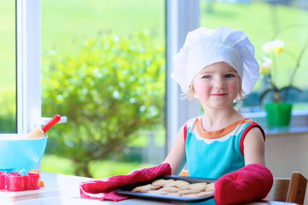 little girl practicing safety while baking treats